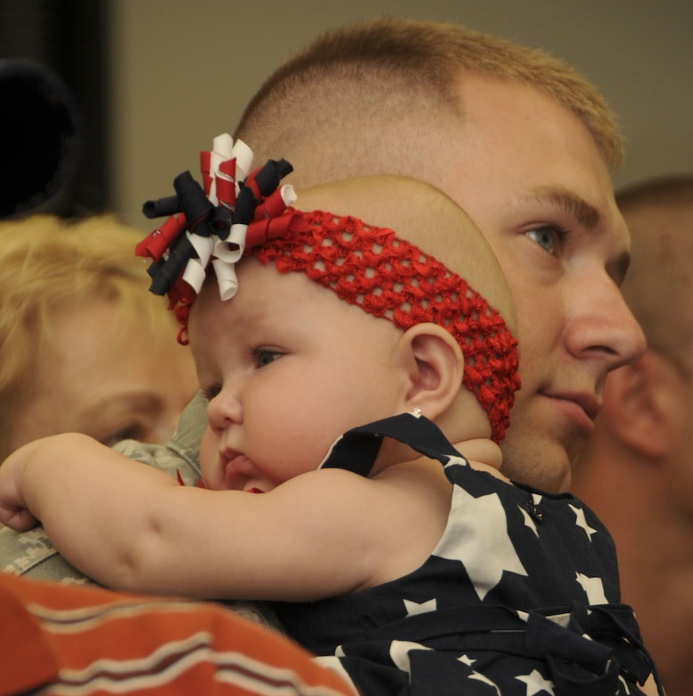 Senior Airman Jeffrey Stich, a member of the 108th Security Forces Squadron, a New Jersey Air National Guard unit, holds his daughter, Kyleigh, during a farewell ceremony at Joint Base McGuire-Dix-Lakehurst on July 12, 2011. Stich, along with about 30 other security forces members, have deployed to Southwest Asia in support of Operation New Dawn where they will be responsible for maintaining security at the air base. (U.S. Air Force photo/Airman Kellyann Novak)