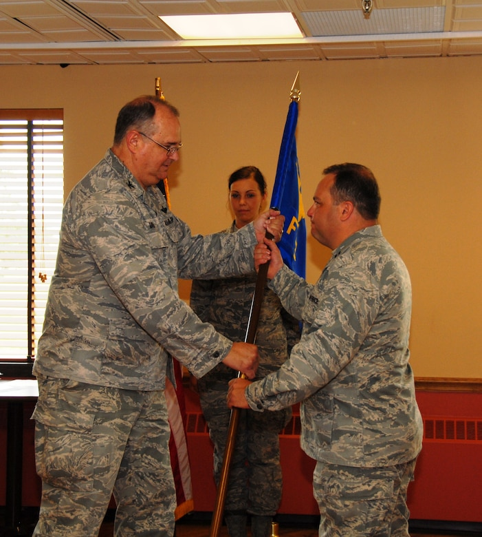 Captain Bryan Dalporto (on right) assumed command of the 107th Airlift Wing's Force Support Squadron in a ceremony recently held here. The captain previously held the position as the 107 AW Services Squadron commander and replaces outgoing Commander Lt. Col. Linda Blaszak. The captain is now responsible for more than 100 Airmen. Passing the FSS Guidon is the 107th Mission Support Commander Col. Timothy Vaughan. (U.S. Air Force photo/Tech. Sgt. Justin Huett)