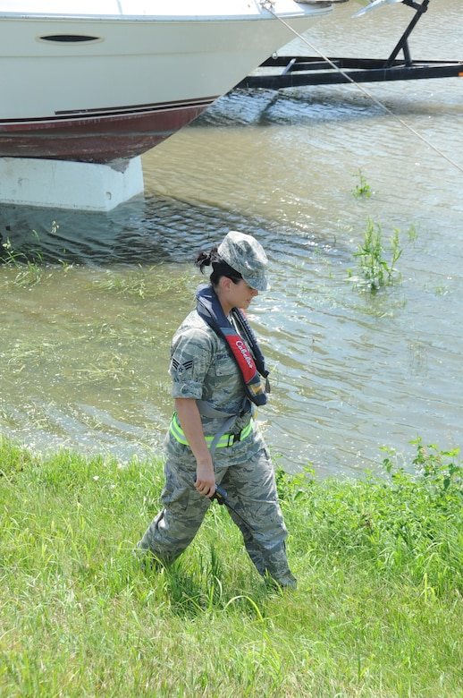 Senior Airman Sara Chadwick, a 22-year-old Madison, Neb., native, a medical technician with the Lincoln-based 155th Air Refueling Wing, inspects a portion of levee near Omaha's now-flooded Freedom Park June 30. Chadwick is one of 28 Nebraska Air National Guardsmen that volunteered to serve on state active duty in the Nebraska National Guard's ongoing response to the 2011 flood (Army photo by Sgt. Koan Nissen).