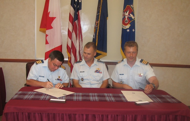 LCol Joe MacMillan, left, outgoing Commanding Officer of Canadian Detachment Rome, and LCol Dave Pletz, right, incoming Commanding Officer, sign formal orders as part of the change-of-command ceremony. BGen Chris Coates, the Deputy Commander of the Continental U.S. NORAD Region, center, served as the Presiding Officer for the ceremony.