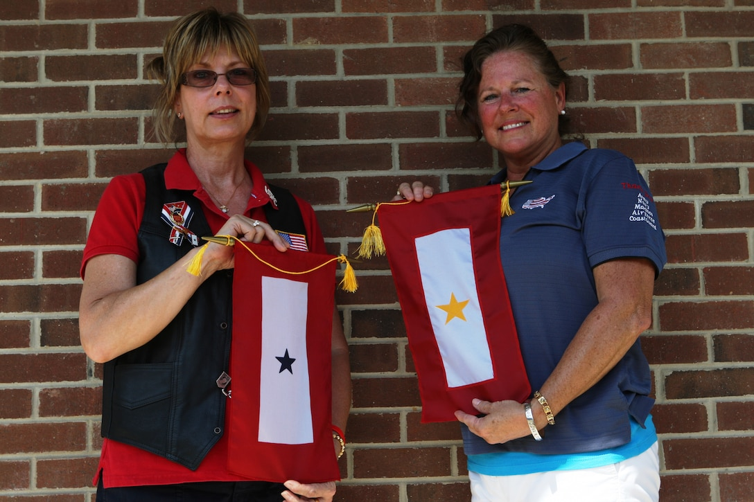 Colleen Greene (left) and Deb Tanish stand with their respective blue and gold star flags; the blue symbolizing that they either have a son or daughter in the armed forces and the gold meaning a son or daughter who has died while in the service. Following her son's death in 2004, Tanish has made it her mission to spread the stars meaning and the knowledge of various support groups for blue and gold star parents who do not realize the support system available to them.
