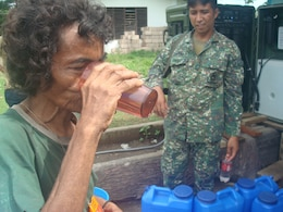 An elderly woman drinks a glass of purified water she received, July 14, from a Filipino Marine operating an Aspen 2000DM water purification system at a water distribution area in Culandanum, Palaw-an. The armed forces of the Philippines deployed a five-man team with the National Development Support Command to Palaw-an, June 23, for a humanitarian operation to provide aid and prevent the spread of a cholera outbreak.