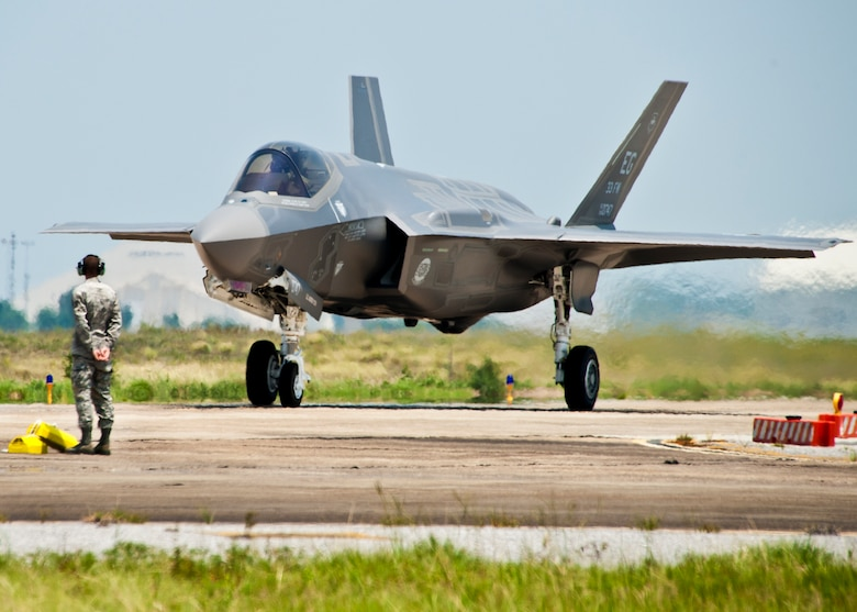A 33rd Fighter Wing maintainer watches as the first F-35 Lightning II joint strike fighter taxis in to its new home at Eglin Air Force Base, Fla., July 14.  (U.S. Air Force photo/Samuel King Jr.)