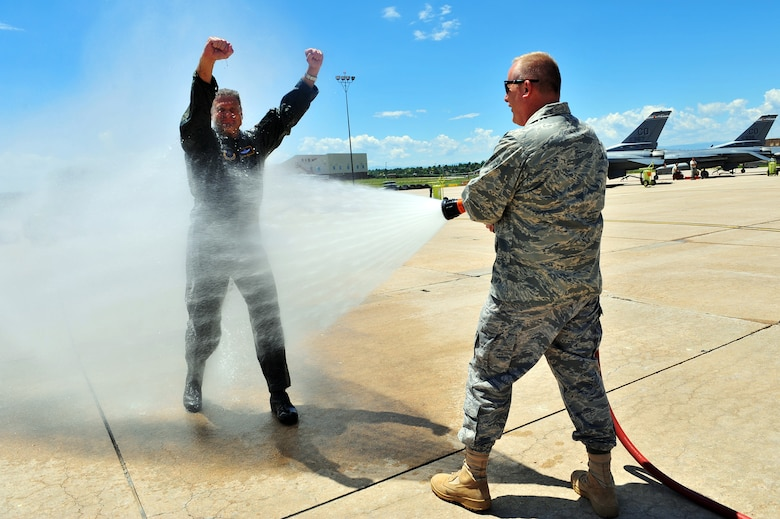 BUCKLEY AIR FORCE BASE, Colo. -- Colonel Trent Pickering, 460th Space Wing vice commander gets sprayed down by Col. Daniel Dant, 460th SW commander, after his incentive flight here July 13.