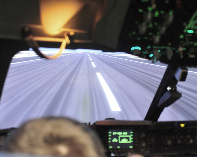 "Evan Waara, ""Pilot for a Day,"" attempts to ""land"" while on a C-17 aircraft simulator July 7 at Joint Base Lewis-McChord, Wash. The simulator was only one of several events during Evan's participation in the Pilot for a Day program. (Air Force photo/Staff Sgt. Frances Kriss)"