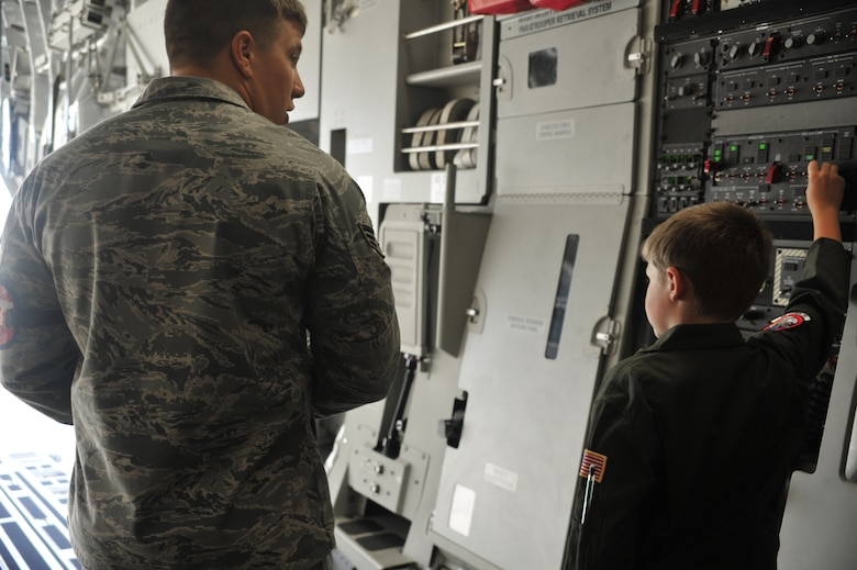 "Senior Airman Stephen Lanham, 62nd Aircraft Maintenance Squadron crew chief, instructs Evan Waara, ""Pilot for a Day,"" on how to open the ramp doors of a C-17 Globemaster III July 7 at Joint Base Lewis-McChord, Wash. Evan also had an opportunity to sit in the cockpit of the C-17. (Air Force photo/Staff Sgt. Frances Kriss)"