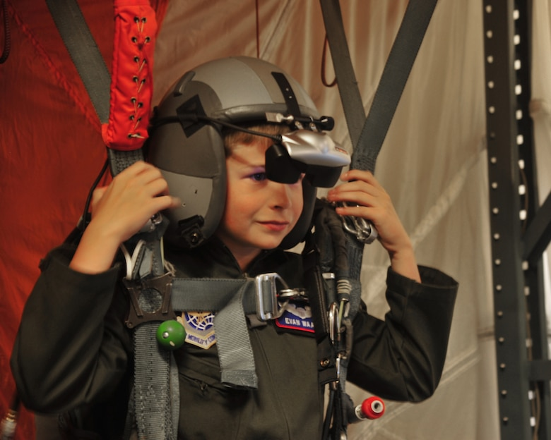 "Evan Waara, ""Pilot for a Day,"" prepares to ""parachute"" and land on a simulated naval ship July 7 at Joint Base Lewis-McChord, Wash. Evan had an opportunity to be strapped on a virtual reality parachute simulator as part of the Pilot for a Day Program. (Air Force photo/Staff Sgt. Frances Kriss)"