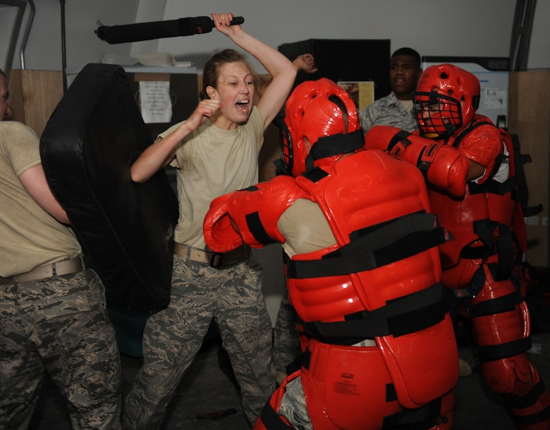 Cadet Yannie Horth yells out commands at two attackers during a baton training drill with the 380th Expeditionary Security Forces Squadron. Horth is here as part of Operation Air Force-Deployed, a program designed to give cadets a firsthand view of a deployment. (U.S. Air Force photo/Master Sgt. Chance Babin)