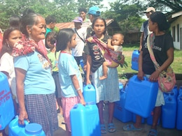 Local people line up with five-gallon water jugs, July 15, to receive purified water at a water distribution area in Culandanum, Palaw-an. A cholera outbreak was declared, April 1, in Culandanum after at least 11 people died due to severe diarrhea, vomiting and dehydration believed to be caused by contaminated water.