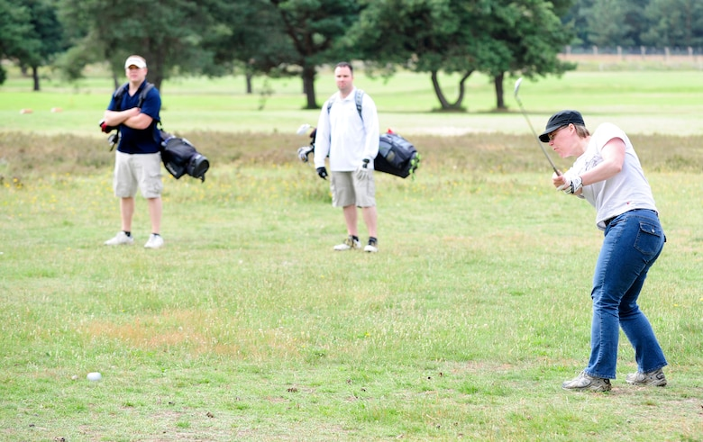 RAF MILDENHALL, England -- Cassandra Denton, 100th Communications Squadron, plays a punch shot under the trees on the 11th hole during the RAF Mildenhall Intramural Golf play-offs at Breckland Pines Golf Club, RAF Lakenheath, July 12, 2011. Brian Szarek (blue shirt) and Jonathan Barnes (white shirt), playing in opposition for the 100th Maintenance Squadron, were one hole up on the back nine. (U.S. Air Force photo/Senior Airman Ethan Morgan)