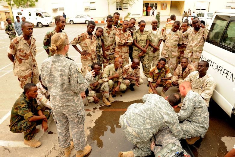 DJIBOUTI CITY, Djibouti - Combined Joint Task Force-Horn of Africa medical professionals demonstrate how to treat and load an injured soldier onto a litter during a week-long medical seminar, July 7. U.S. servicemembers shared their procedures for providing immediate care and treatment of injured soldiers whether at home station or in a remote environment with their Djiboutian counterparts. (U.S. Air Force Photo Master Sgt. Ray Bowden)