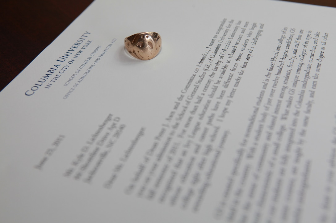 A solid gold ring baring the Marine Corps emblem, which was purchased by Cpl. Kyle Lichtenberger's great-grandfather in 1918, rests on top of his acceptance letter from Columbia University in New York, at his home in Jacksonville, N.C. July 15. Kyle is the fourth generation of his family to serve in the Marine Corps. He received the ring on his wedding day January 26, 2008. (Official U.S. Marine Corps Photo Illustration by Sgt. Richard Blumenstein)