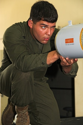 Cpl. John A. Moore, a Marine Aviation Logistics Squadron 12 aviation ordnance technician, aligns a part of the Guided Bomb Unit-12 he is working on before torqueing it down to the unit in a warehouse on the flightline here in support of exercise Talisman Sabre 2011 July 19. The MALS-12 service members are slated to provide thousands of pounds of live ordnance during the course of the exercise.