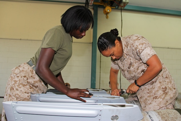 Lance Cpl. Shaylin Cobb, a Marine Aviation Logistics Squadron 12 aviation ordnance technician, observes Pfc. Justine Mcpeters, a Marine Aircraft Group 12 ground supply clerk, as she torques the fins onto a Guided Bomb Unit-12 in a warehouse on the flight line here in support of exercise Talisman Sabre 2011 July 19. Although the focus for the ordnance Marines has been to train with their Australian counterparts and to build bombs in support of the exercise, Talisman Sabre has also given Marines here the opportunity to cross train into different military occupational specialties.