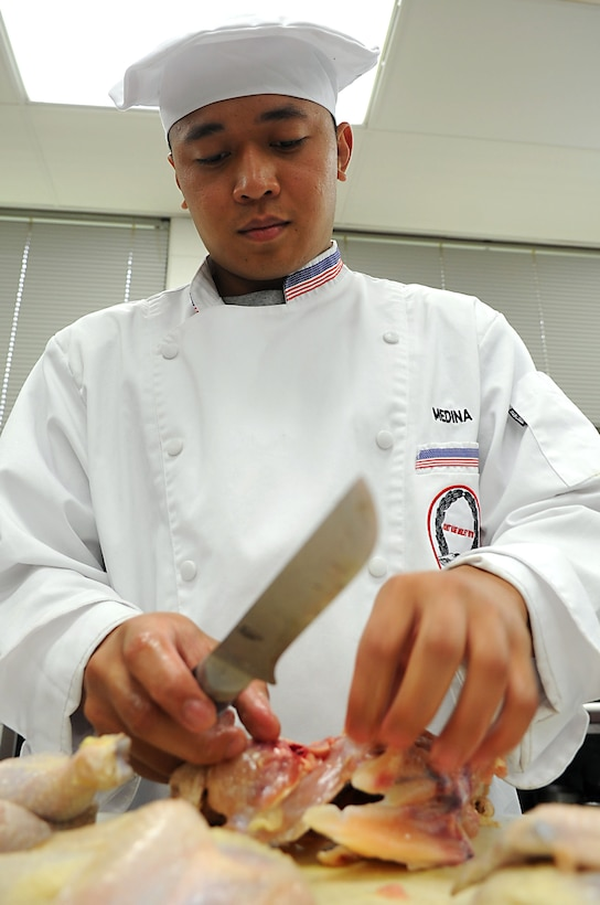 Staff Sgt. Ghil Medina, 633rd Force Support Squadron services journeyman, prepares chicken for a practice presentation during training at Fort Lee, Va., July 13, 2011. Sergeant Medina will compete for the distinction of becoming the American Culinary Federation's National Student Chef of the Year Award at the 2011 ACF National Convention in Dallas.  (U.S. Air Force photo by Airman 1st Class Kayla Newman/Released)