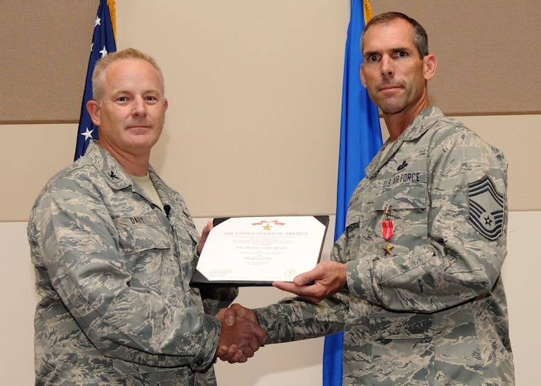 BUCKLEY AIR FORCE BASE, Colo. --  Colonel Daniel Dant, 460th Space Wing commander, awards the Bronze Star to Chief Master Sgt. Todd Kennedy, 460th Communications Squadron July 15, 2011. Kennedy received the Bronze Star for leading his troops in a combat environment. His exceptional leadership and battlefield presence were crucial to the squadron's mission capability as well as the integrated execution of joint and coalition counter-insurgency operations. (U.S. Air Force photo by Airman1st Class Marcy Glass)