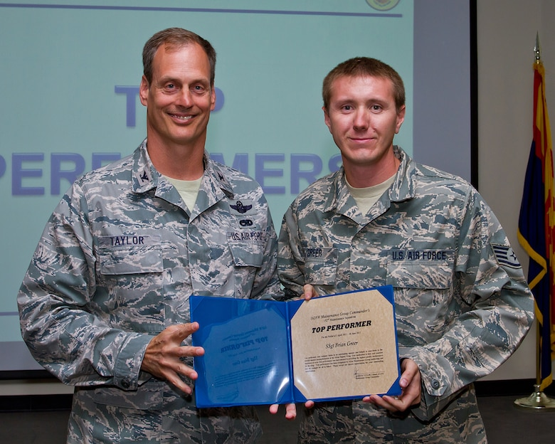 Col. James Taylor (left) presents Staff Sgt. Brian Greer the Top Performers Award for his work with the 152nd Fighter Squadron. (U.S. Air Force photo/Senior Airman Chris Heising)