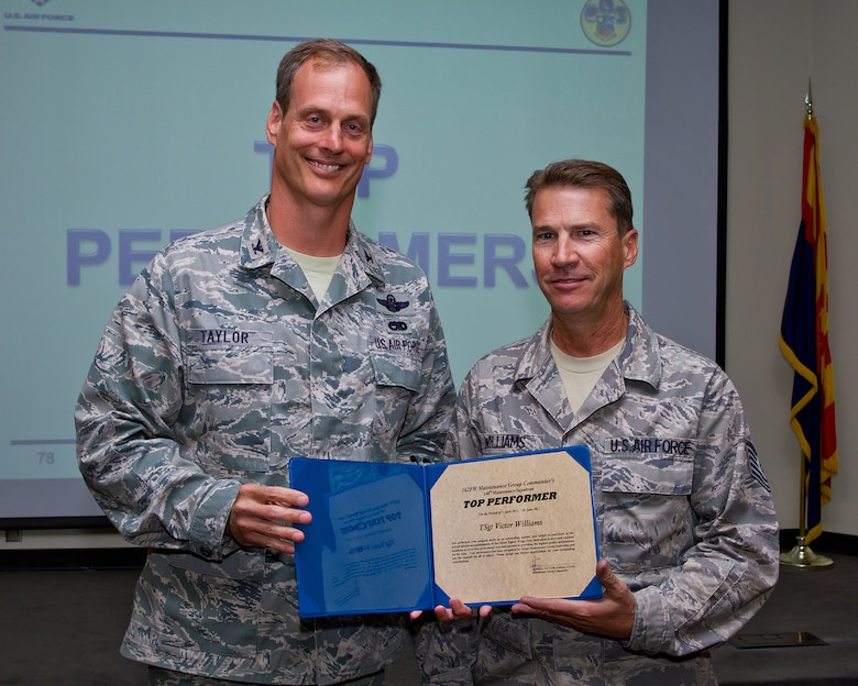 Col. James Taylor (left) presents Tech. Sgt. Victor Williams the Top Performers Award for his work with the 148th Fighter Squadron. (U.S. Air Force photo/Senior Airman Chris Heising)