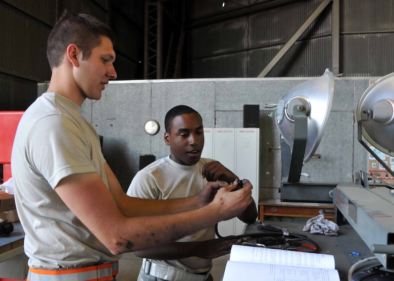 Staff Sgt. Jesse D. Albrecht offers Airman 1st Class Christopher L. Petty some On-the-Job-Training while performing routine maintenance on a light cart while deployed in Western Europe at the 313th Air Expeditionary Wing on July 19, 2011. (U.S. Air Force phot/Capt. John P. Capra)