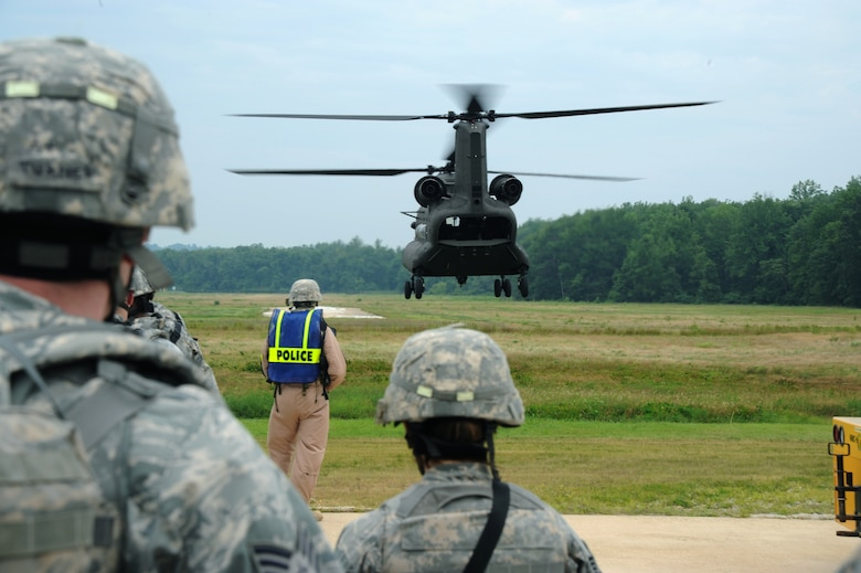 Defenders from the 11th Security Forces Squadron wait to board a Maryland Army National Guard CH-47 Chinook from Bravo Company, 3-126th General Support Aviation Battalion at Weide Army Airfeild, Va., during a training exercise at Davidson Army Airfeild on June 19.  The goal of the training was to familiarize servicemembers with procedures to enter, exit and defend helicopters in a deployed environment. (U.S. Air Force photo by Senior Airman Torey Griffith)