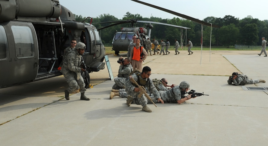 Airmen from the 11th Wing Security Forces Squadron and Soldiers from the 55th Signal Company unload from a static CH-60 Black Hawk as they train for airborne operations at Davidson Airmy Airfeild, Va., July 19.  The training familiarized servicemembers with getting in to and out of helicopters in a deployed environment.  Combat Cameramen from the 55th Signal Company embedded with the Defenders as they trained combat operations as well. (U.S. Air Force photo by Senior Airman Torey Griffith)