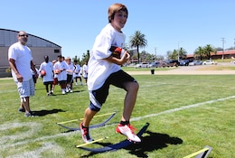 Justin Lynell, 11, conducts a speed and agility exercise during the Eric Dickerson Youth Football Camp at Camp Pendleton's 11-Area football field, July 21. Children ages 7-18 were eligible to take part in hands-on instruction from former NFL players while also learning offensive and defensive drills.