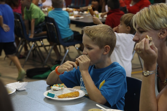 C.J. Czepiel, Summer Enrichment Program participant, takes a bite of a corndog durring the end of Summer Enrichment Program potluck at the Matthew C. Perry Elementary School gym here July 21. The program was a month-long and students learned and attempted to solve some of Earth's many mysteries.