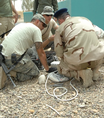 Senior Airman Juan Ramirez and Airman 1st Class Dillon Boutin, both 332nd Expeditionary Civil Engineer Squadron electrical systems journeymen, work with U.S. civilians and Iraqi Airmen to help repair a fountain in front of the Iraqi Air Force Headquarters building at Joint Base Balad, Iraq, July 20. Ramirez is deployed from Andrews Air Force Base, Md., and is a native of Las Vegas, Nev., and Boutin is deployed from Altus AFB, Okla., and is a native of Layfayette, La. (U.S. Air Force photo by Senior Airman Amber R. Kelly-Herard)