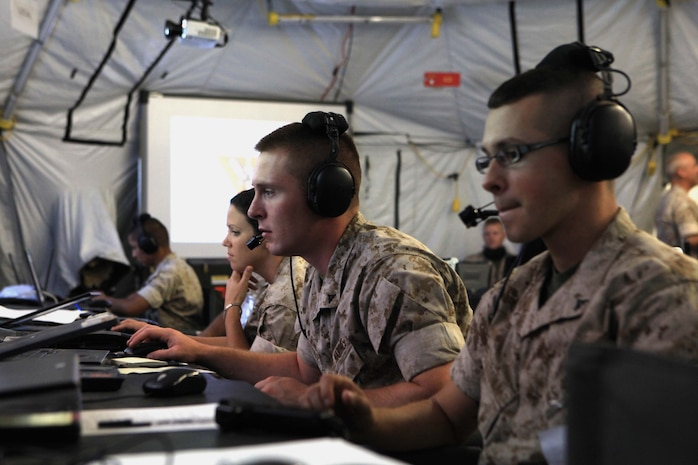 Marine tactical air command squadron 48 Marines receive aircraft and ground troop information on their monitors during Operation Javelin Thrust at Marine Corps Air Station Yuma, Ariz., July 24. The information received is then passed on to the various combat elements in the training exercise to keep them informed on current operations.