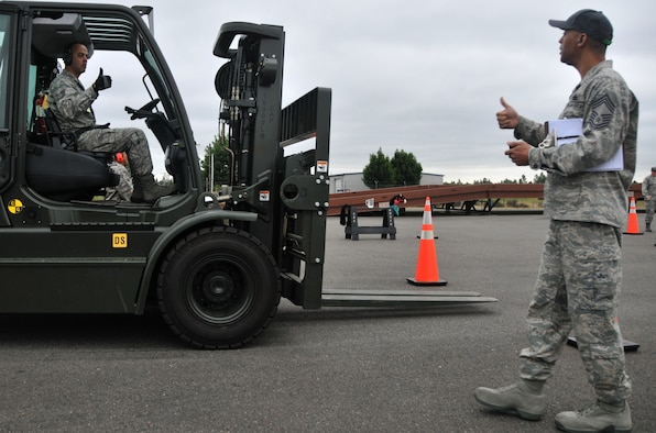 An Airman signals ?all clear? to an umpire during a forklift driving course, July, 25, 2011, at Joint Base Lewis-McChord, Wash. The event was part of Air Mobility Rodeo 2011, a biennial international competition that focuses on mission readiness, featuring airdrops, aerial refueling and other events that showcase the skills of mobility crews from around the world.  (U.S. Air Force photo/ Airman 1st Class Jared Trimarchi)