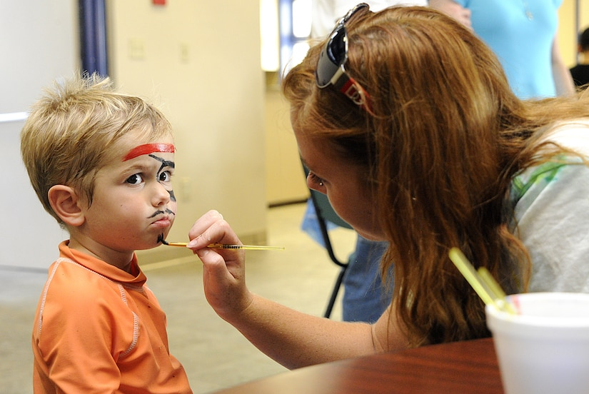 Two year-old Landon Zoss, son of Ensign Brandon Zoss stationed at the Nuclear Power Training Unit, has his face painted by volunteer Brandi Horne during the Water Park Wonderland event hosted by Balfour Beatty at Joint Base Charleston-Weapons Station, July 22.   (U.S. Navy photo/ Mass Communication Specialist 3rd Class Brannon Deugan)