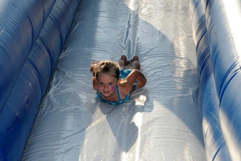 Four year old Brianna Stockwell, daughter of Staff Sgt. Seth Stockwell, slides down an inflatable water slide during the Water Park Wonderland event hosted by Balfour Beatty at Joint Base Charleston-Weapons Station, July 22.  The event kicked off the annual Resident Satisfaction Survey in which residents of JB CHS-WS base housing offer feedback to Balfour Beatty about the services being provided in the community. (U.S. Navy photo/ Mass Communication Specialist 3rd Class Brannon Deugan)