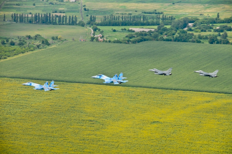 Ukraine SU-27s fly with Alabama Air National Guard F-16 Fighting Falcons over Ukranian sunflower fields during SAFE SKIES 2011.  SAFE SKIES 2011 is a military-to-military exchange between airmen from the U.S., Ukraine and Poland to enhance airspace security over the Ukraine and Poland in preparation for EURO 2012, the European soccer championship games. (U. S. Air Force photo/Tech. Sgt. Charles Vaughn)