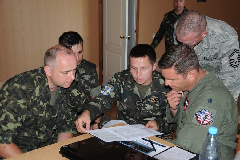 Lt. Col. Robert Swertfager, from the California Air National Guard's 144th Fighter Wing in Fresno, discusses the itinerary for SAFE SKIES 2011 with his Ukrainian counterparts July 16, 2011.  SAFE SKIES 2011 is a military-to-military exchange between airmen from the U.S., Ukraine and Poland to enhance airspace security over the Ukraine and Poland in preparation for EURO 2012, the European soccer championship games. (U. S. Air Force photo/Tech. Sgt. Charles Vaughn)