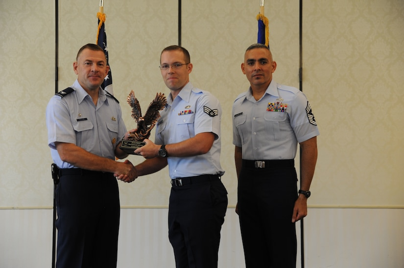 Col. Richard McComb and Chief Master Sgt. Jose LugoSantiago present Senior Airman Steven Williams a statue in recognition of his being selected as a 628th Air Base Wing quarterly award winner, July 25 at Joint Base Charleston – Air Base. Other 628 ABW quarterly award winners included Senior Airman Laura Yang, Staff Sgt. Tahara Burchell, Master Sgt. Diana Tamayo, 1st Lt. Ryan Peake, Capt. Aaron Cohenour, Airman 1st Class Pativa Brice, Paul Valentine and Cheryl Bennett. McComb is the Joint Base Charleston commander, LugoSantiago is the 628 ABW command chief and Williams is assigned to the Honor Guard. (U.S. Air Force photo/Staff Sgt. Nicole Mickle)