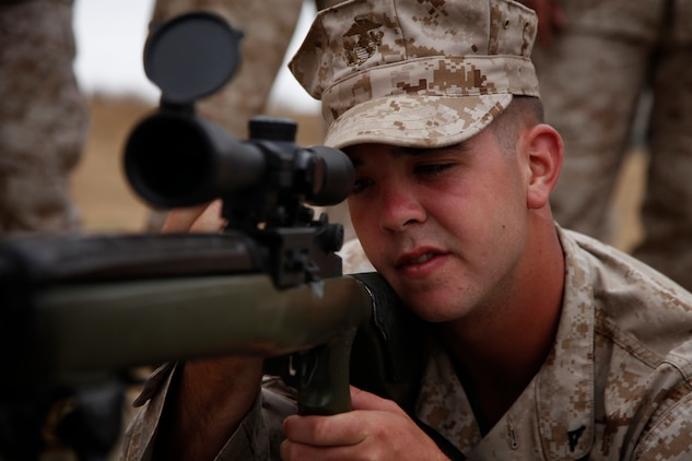 Lance Cpl. John H. Fulton, administrative clerk, 15th Marine Expeditionary Unit (MEU) looks down the sights of a Designated Marksman Rifle as a part of a familiarization fire range conducted on Camp Pendleton, July 26-27. Fulton, 20, is a native of Howell, N.J. and has already completed a deployment with the unit and is eagerly looking forward to his next float.