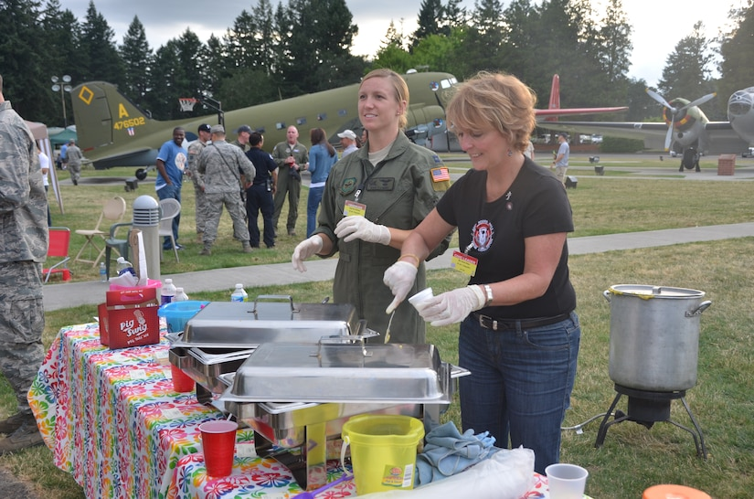 Capt. Keri Fleming and Ms. Karen Elsey from Team Charleston serve shrimp and grits to Airmen and spectators at Ranier Ranch atn Joint Base Lewis-McCHord July 26 during the Air Mobility Command 2011 Rodeo. (U.S. Air Force photo/2nd Lt. Susan Carlson)