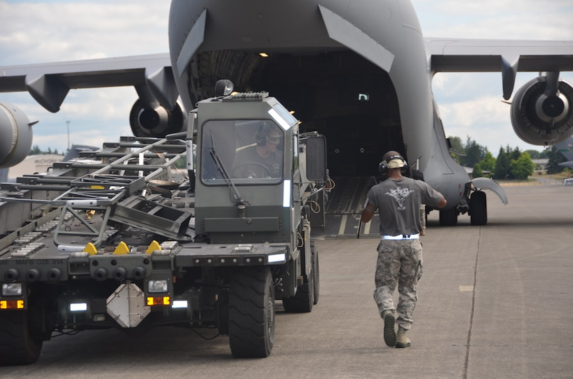 Staff Sgt. Luther Franklin directs Staff Sgt. Nick Sansone, the K-loader operator, during the engine running onload/offload competition July 27 at the Air Mobility Command 2011 Rodeo at Joint Base Lewis-McChord, Wash. (U.S. Air Force photo/2nd Lt. Susan Carlson)