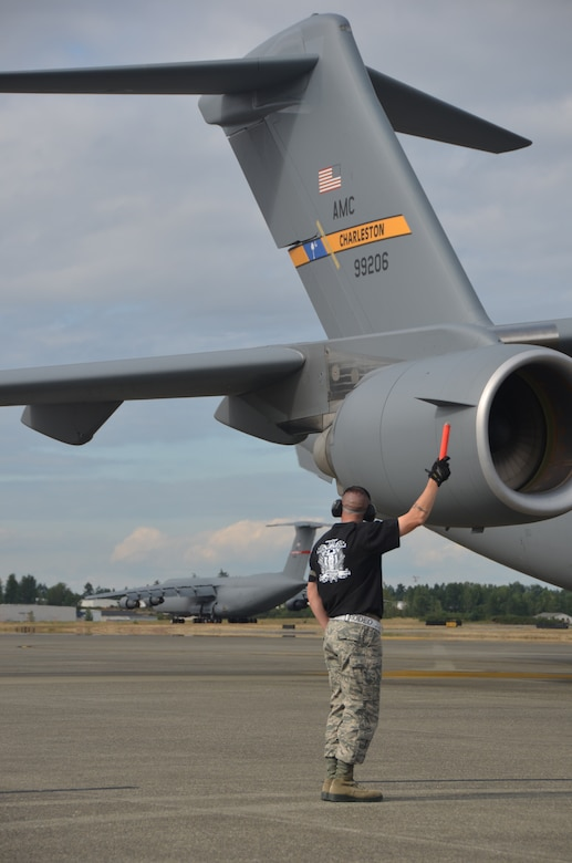 Tech. Sgt. Jessy Martin guides the Team Charleston C-17 Rodeo jet during the Air Mobility Rodeo 2011 July 27 at Joint Base Lewis McChord, Wash. Martin is from the 437th Aircraft Maintenance Squadron. (U.S. Air Force photo/2nd Lt. Susan Carlson)