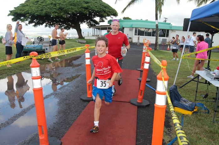 Bradley and Lucien Parker cross the finish line together at the Marine Corps Community Services Hawaii Camp H.M. Smith Semper Fit Center's 15th annual 5K Grueler here. The race is held every year to raise funds for the U.S. Marine Corps Forces, Pacific birthday ball.