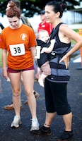 Kathrine J. Harris (right), with her two daughters, Taylor (left) and Jayna Harris, cools off just after crossing the finish line of the Marine Corps Community Services Hawaii Camp H.M. Smith Semper Fit Center's 5K Grueler. Harris competed in the race with her infant child and older daughter.