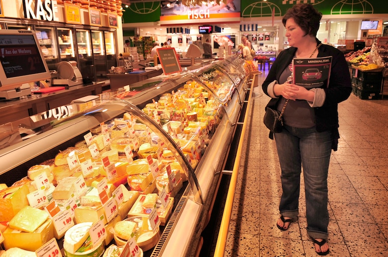 """Melanie Robinson wife of Airman 1st Class Clark Robinson an information assurance technician with the 693rd Intelligence Support Squadron, looks at the cheese selection at a local grocery store during the first What is What class by the Airman & Family Readiness Center, May 26, 2011. """"This tour has been extremely helpful, because normally just walking in would be intimidating,"""" said Mrs. Robinson. The program was designed to give hands on experience to members of the Department of Defense in shopping on the local economy. (U.S. Air Force Photo by. Tech. Sgt. Jocelyn L. Rich)"""