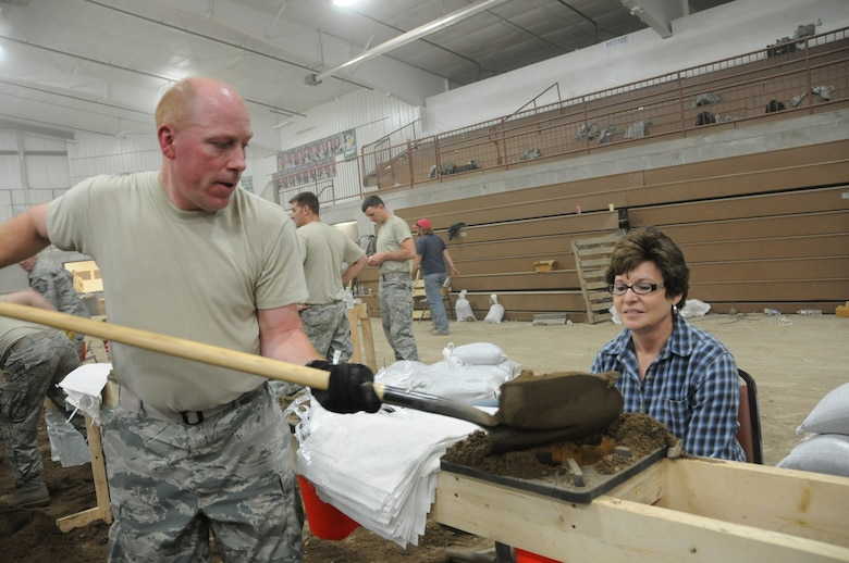 FT. PIERRE, S.D. -- Capt. Kevin Miller, Budget Officer for the 114th Financial Management Flight, works with Donna Brown-Glow, a Wood, S.D. and Ft. Pierre resident to fill sandbags late into the evening on May 31. Brown-Glow's home has not been threatened by the flooding, but feels it's important to help others throughout the state.(Photo by Capt. Michael Frye, 114th Fighter Wing Public Affairs Officer) (RELEASED)