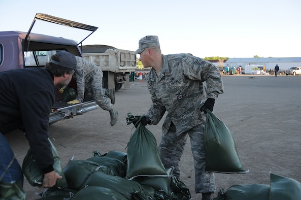 PIERRE, S.D. -- Tech. Sgt. Eric Hoogendoorn (right) and Staff Sgt. Adam Groff, both from the 114th Fighter Wing Civil Engineers, help Pierre resident Deloren Krieger load sandbags into his vehicle. To date, more than 900 Soldiers and Airmen from the South Dakota National Guard have been called to support the flood fighting efforts along the Missouri River. (SDNG photo by Capt. Michael Frye, 114th Fighter Wing Public Affairs Officer) (RELEASED)