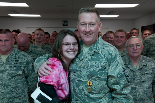 Tech. Sgt. Roy L. Akers, a civil engineer with the 130th Civil Engineering Squadron, 130th Airlift Wing, Charleston, W.Va., and Ashley N. Parker, a civilian, pose for a picture in front of the 130th CES formation during an awards ceremony, Feb. 6. Tech. Sgt. Akers received the Air Force Commendation Medal for his actions on Aug. 13, 2010, in which he saved Parker's life. (U.S. Air Force photo by Tech. Sgt. Eugene R. Crist)