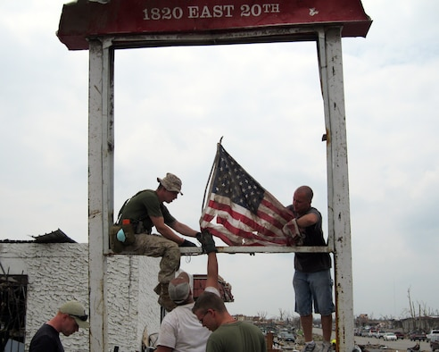Volunteers fly a tattered American flag from a street sign in Joplin, Mo., May 28, 2011. Sixteen Airmen from Altus Air Force Base delivered donations to Joplin, as well as helped search for survivors May 27-28. (Courtesy photo)
