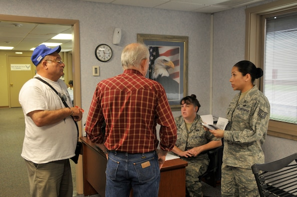 Tech. Sgt. Jessica Gray, customer support non-commissioned officer in-charge, and Staff Sgt. Kerry Godfrey, customer support supervisor, review a veteran's paperwork in the Customer Service and ID Card office. (Air Force photo by Brian Schroeder)