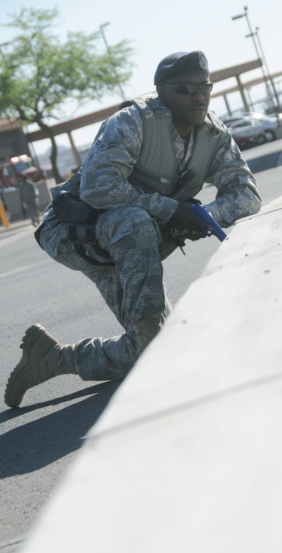 U.S. Air Force Airman 1st Class Lee Jackson, 161st Security Forces Squadron member, executes 360 degrees of surveillance as part of a simulated active shooter exercise at the 161st Air Refueling Guard base, Phoenix, June 4, 2011. This exercise brings together members of the Air National Guard, the Phoenix Police Department, the Federal Aviation Administration and the Transportation Security Agency in order to improve interagency communication. (U.S. Air Force photo by Staff Sgt. Courtney Enos/Released)