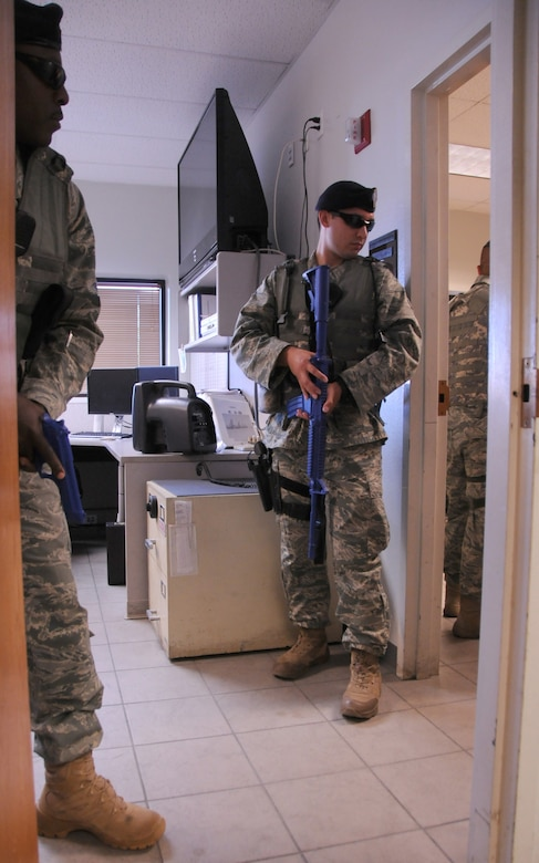 U.S. Air Force Airman 1st Class Lee Jackson (left) and Senior Airman Joshua Ridgley, 161st Security Forces Squadron members, clear a room during a simulated active shooter exercise at the 161st Air Refueling Guard base, Phoenix, June 4, 2011. This exercise brings together members of the Air National Guard, the Phoenix Police Department, the Federal Aviation Administration and the Transportation Security Agency in order to improve interagency communication. (U.S. Air Force photo by Staff Sgt. Courtney Enos/Released)