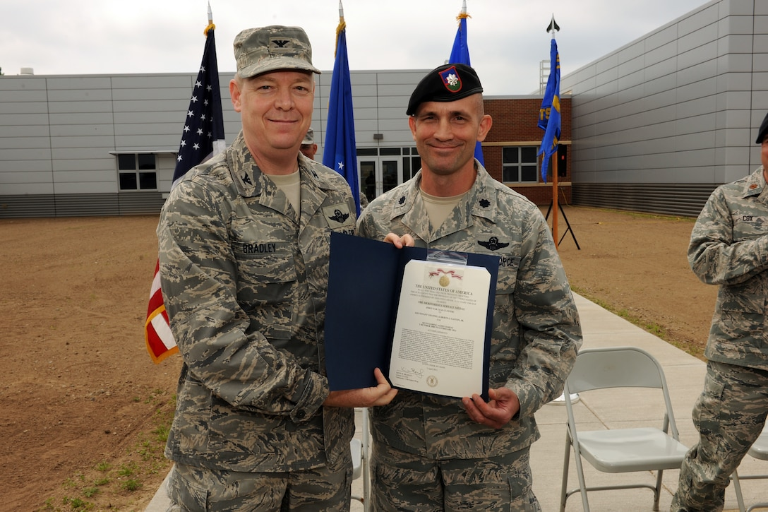 U.S. Air Force Colonel Kevin W. Bradley (left), Commander of the 174th Fighter Wing, presents out-going commander of the 274th Air Support Operations Squadron, Lt. Col. Alberto Gaston, with the Meritorious Service Medal, first oak leaf cluster at Hancock Field Air National Guard Base, Syracuse, NY on June 5, 2011. Lt. Col. Gaston lead the 274 ASOS for three years, and relinquised command to Maj Patrick Cox during a ceremony at the base. (U.S. Air Force photo by Staff Sgt. James N. Faso II).